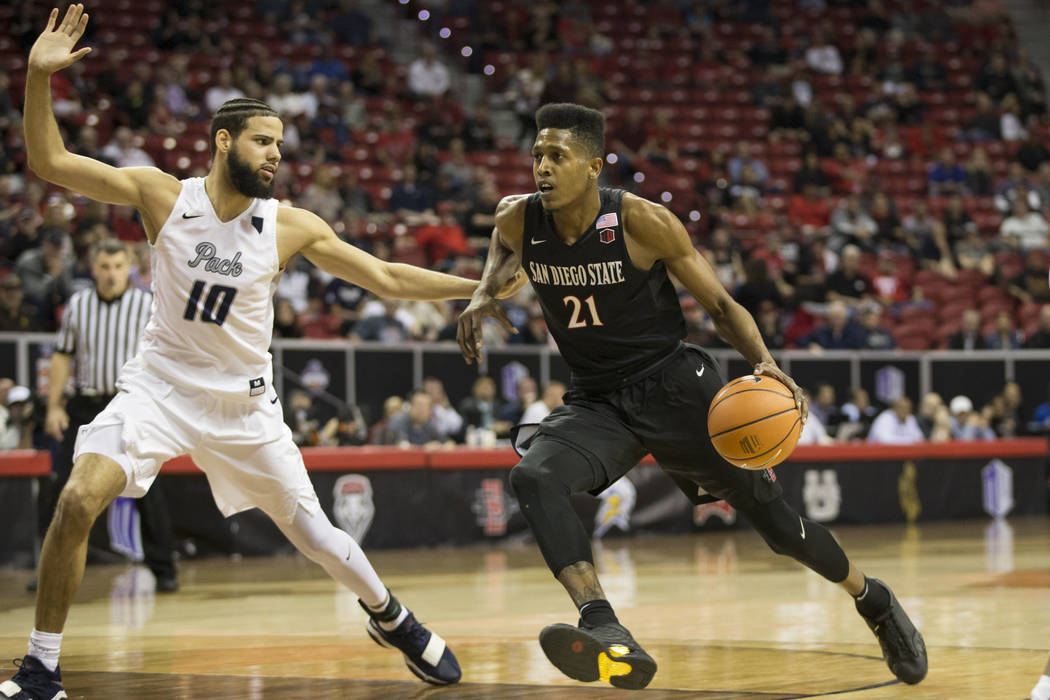 San Diego State Aztecs forward Malik Pope (21) drives to the basket against Nevada Wolf Pack forward Caleb Martin (10) in the first half of the Mountain West Conference men's basketball tournament ...
