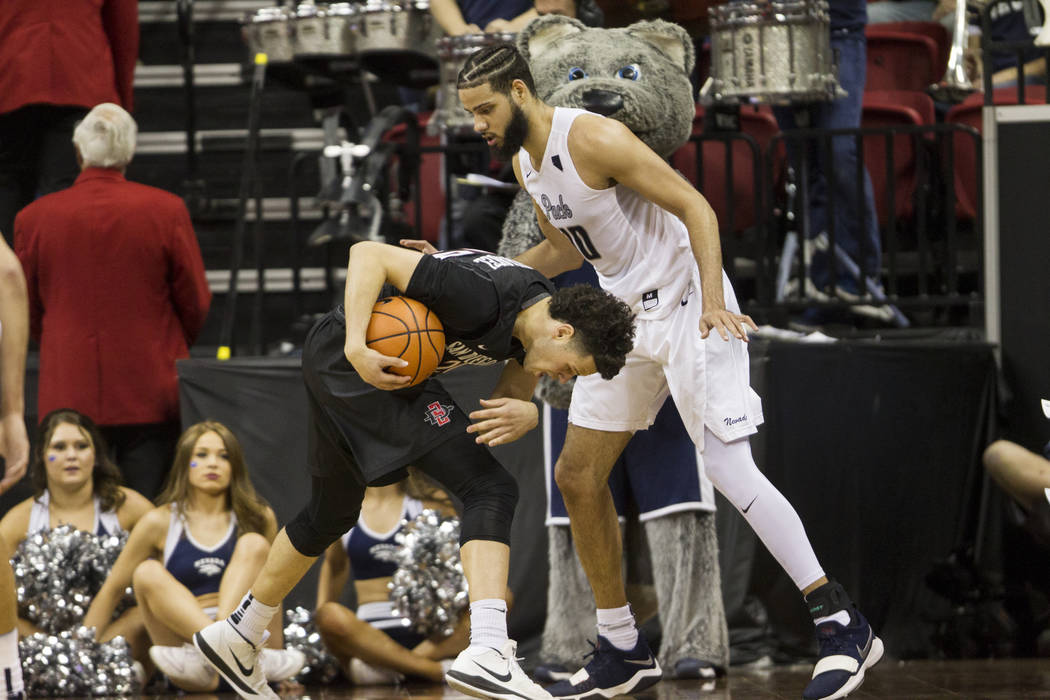 San Diego State Aztecs guard Jordan Schakel (20) is fouled by Nevada Wolf Pack forward Caleb Martin (10) in the second half of the Mountain West Conference men's basketball tournament semifinal ga ...