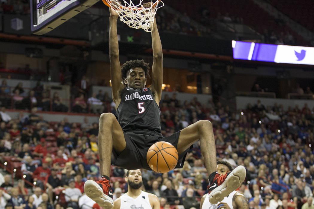 San Diego State Aztecs forward Jalen McDaniels (5) dunks the ball as Nevada Wolf Pack forward Caleb Martin (10) and guard Jordan Caroline (24) look on in the second half of the Mountain West Confe ...