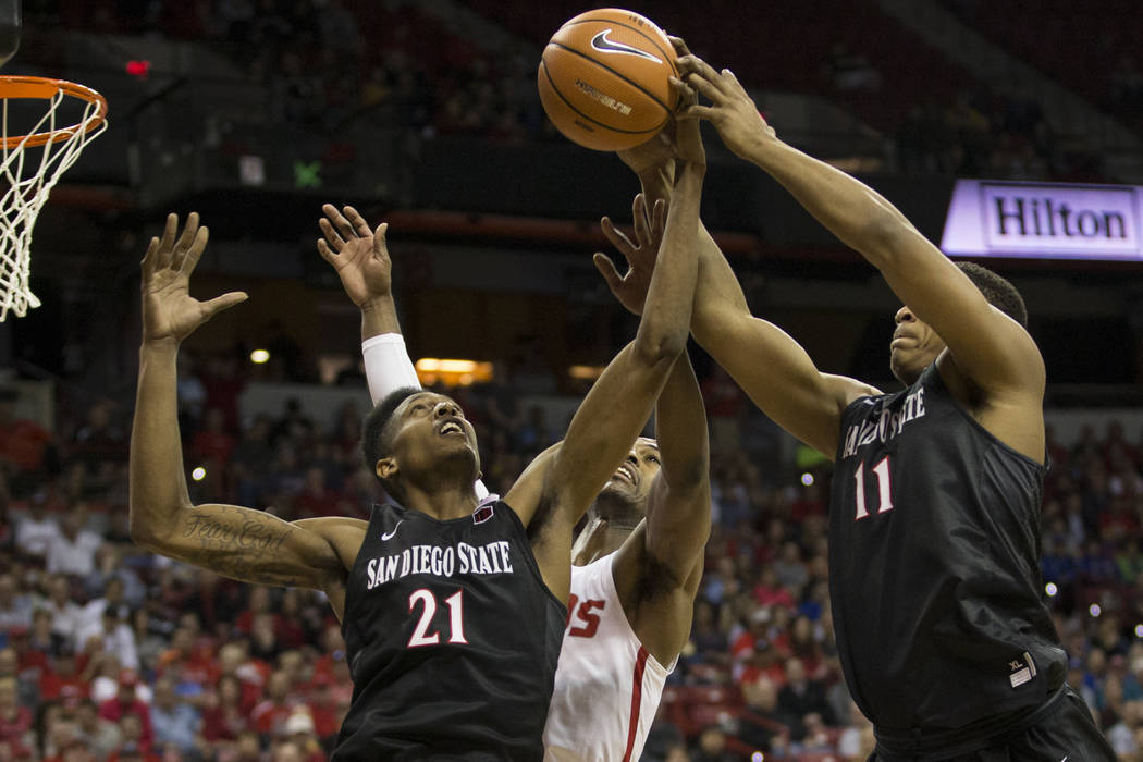 San Diego State Aztecs forward Malik Pope (21) and forward Matt Mitchell (11) fight for the ball against New Mexico Lobos guard Sam Logwood (2) in the first half of the Mountain West Conference me ...