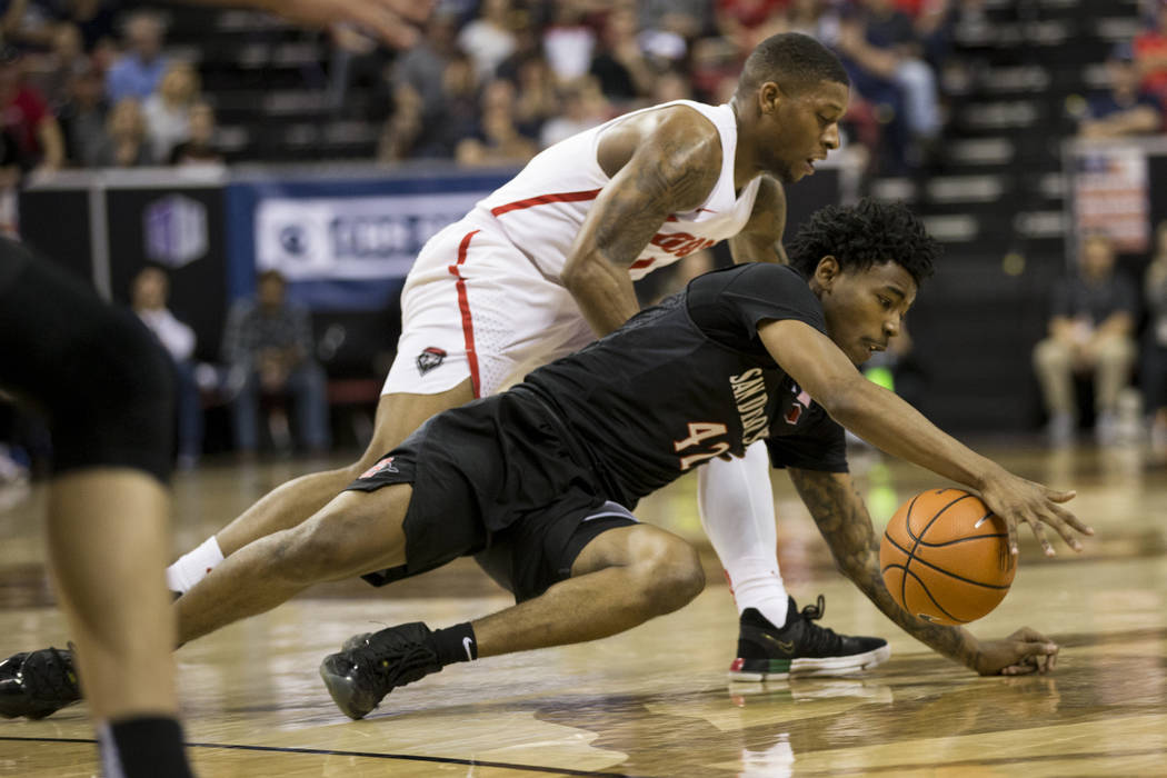 San Diego State Aztecs guard Jeremy Hemsley (42) grabs a loose ball against New Mexico Lobos guard Chris McNeal (1) in the second half of the Mountain West Conference men's basketball tournament f ...