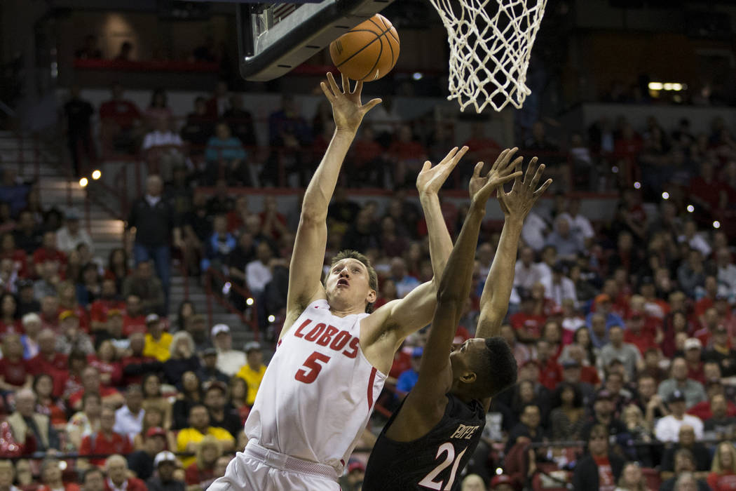 New Mexico Lobos forward Joe Furstinger (5) shoots the ball under pressure from San Diego State Aztecs forward Malik Pope (21) in the second half of the Mountain West Conference men's basketball t ...