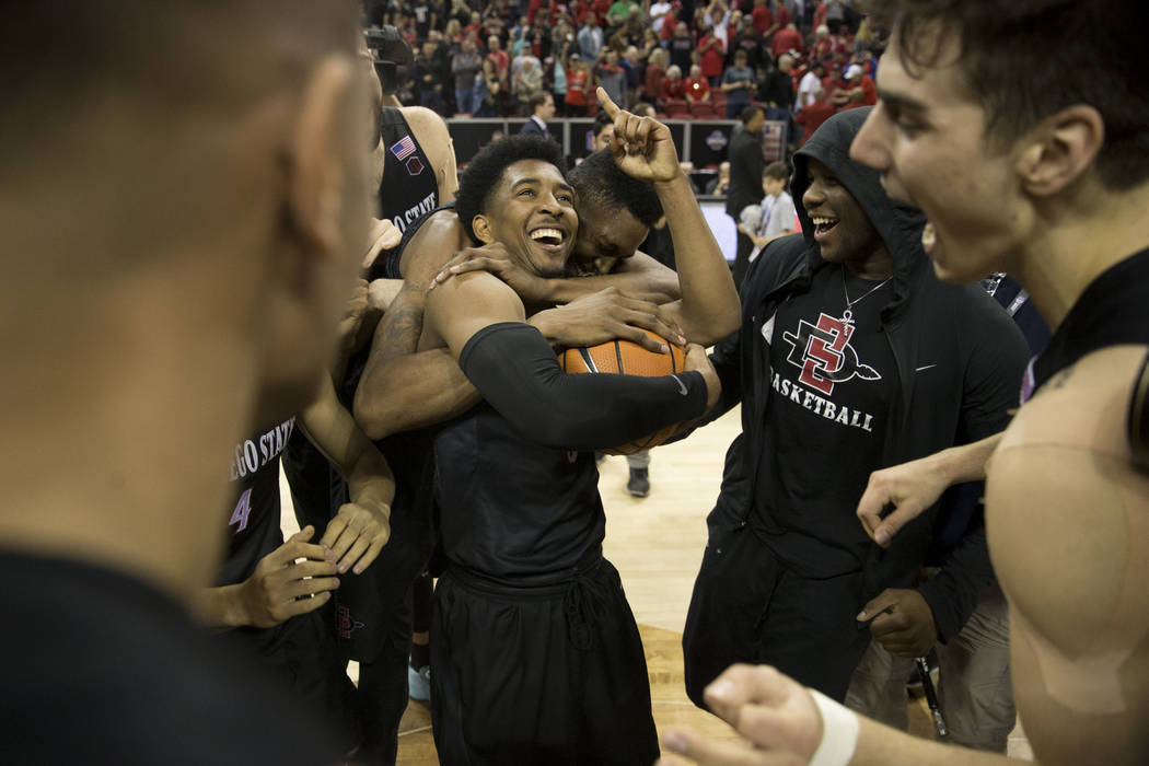 San Diego State Aztecs guard Devin Watson (0) is hugged by forward Malik Pope (21) after their win in the Mountain West Conference men's basketball tournament final at the Thomas & Mack Center ...