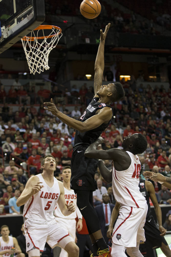 San Diego State Aztecs forward Malik Pope (21) goes up for a shot under pressure from New Mexico Lobos guard Makuach Maluach (10) and forward Joe Furstinger (5) in the first half of the Mountain W ...