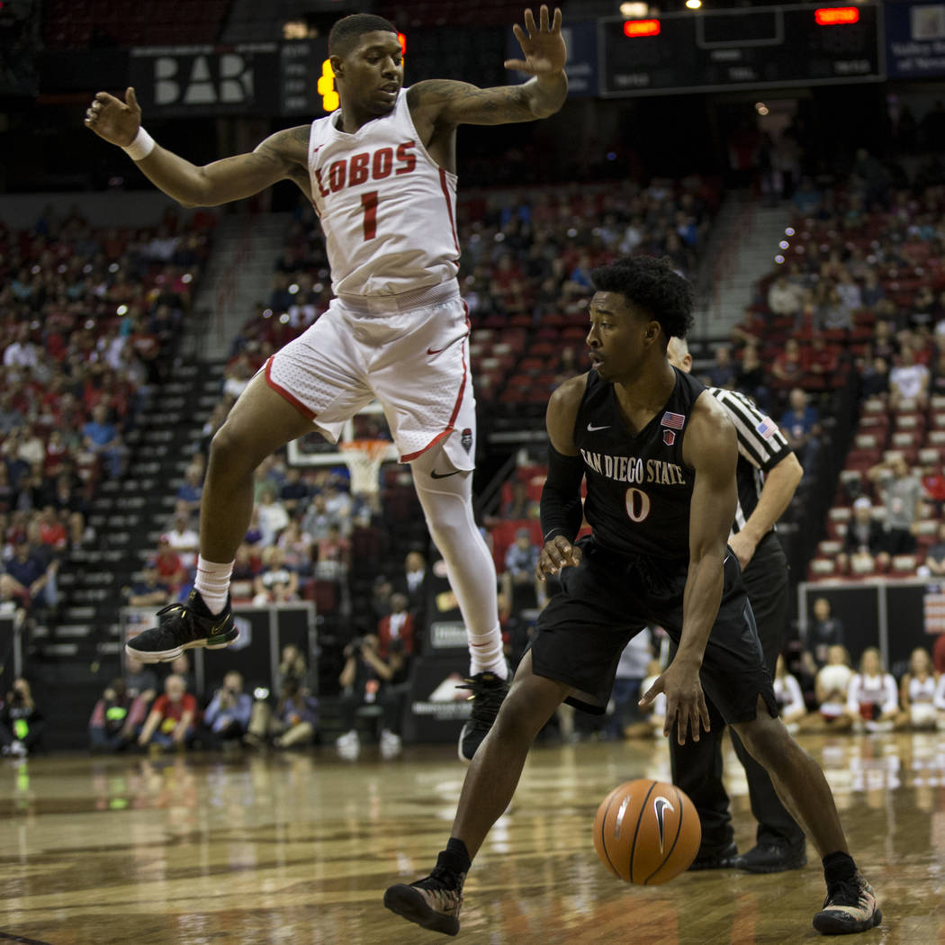 San Diego State Aztecs guard Devin Watson (0) looks to make a play under pressure from New Mexico Lobos guard Chris McNeal (1) in the first half of the Mountain West Conference men's basketball to ...
