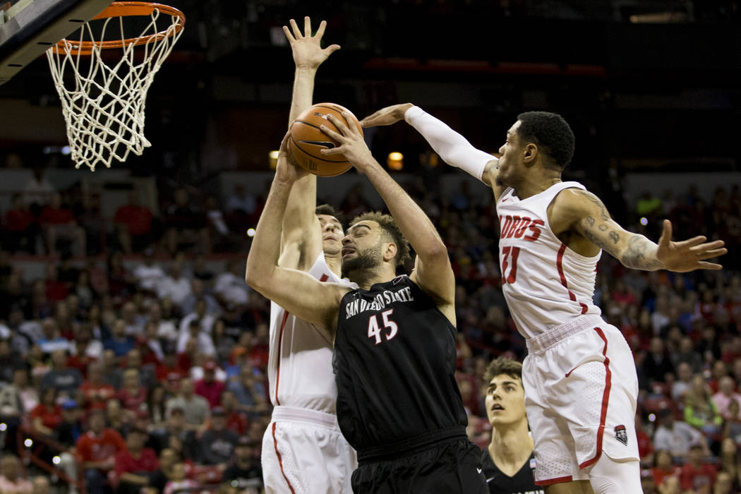 San Diego State Aztecs center Kameron Rooks (45) goes up for a shot under pressure from New Mexico Lobos forward Dane Kuiper (14), left, and forward Jachai Simmons (11), in the first half of the M ...