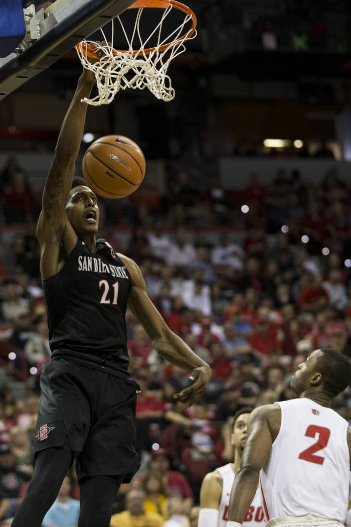 San Diego State Aztecs forward Malik Pope (21) dunks the ball as New Mexico Lobos guard Sam Logwood (2) looks on in the first half of the Mountain West Conference men's basketball tournament final ...