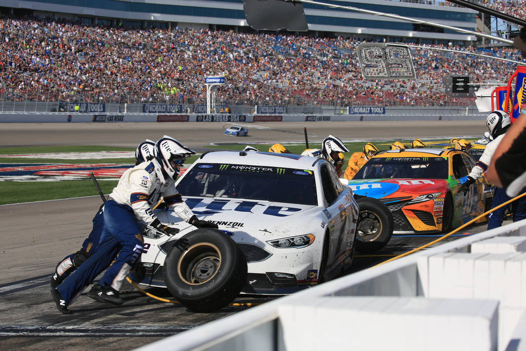 Pit crews from Brad Keselowski (2) and Kyle Busch (18) make final adjustments in the last pit stops of the Monster Energy NASCAR Cup Series Kobalt 400 auto race at Las Vegas Motor Speedway in Las  ...