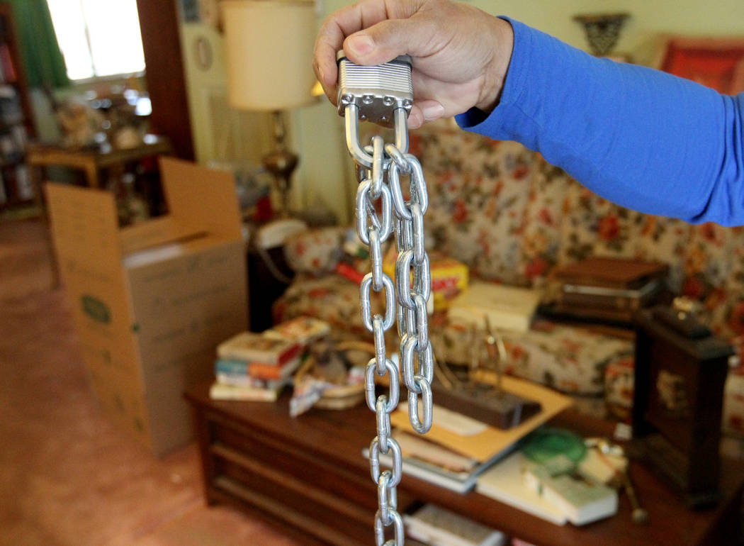 A neighbor show a chain that was cut from a gate at a home at 809 Palmhurst Drive in Las Vegas Thursday, Feb. 22, 2018. After home owner Carole Barnish died last August, Shalena Earnheart claimed  ...
