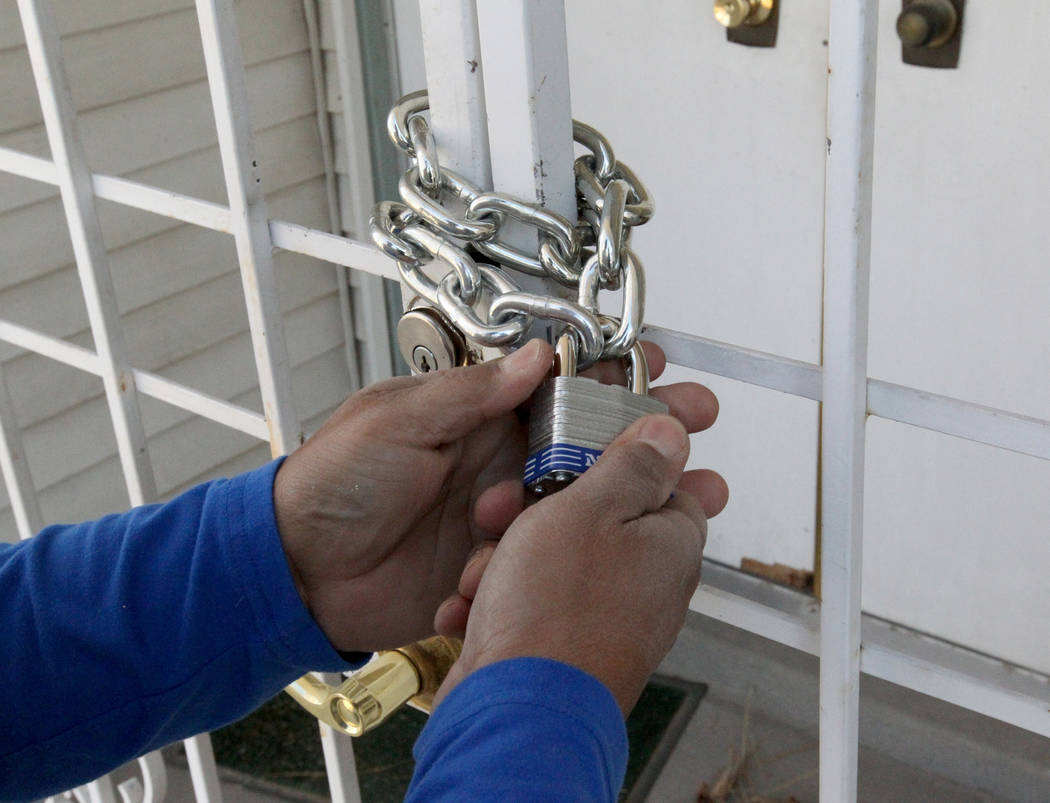 A neighbor locks a chain on the front gate at a home at 809 Palmhurst Drive in Las Vegas Thursday, Feb. 22, 2018. After home owner Carole Barnish died last August, Shalena Earnheart claimed owners ...