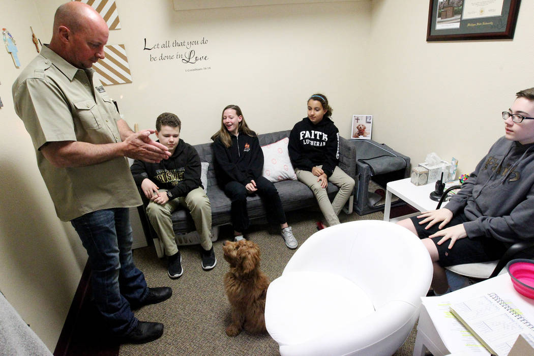 Brad Norton of Norton Dog Training, left, works with Faith Lutheran Middle School and High School therapy dog in training, Esther, at the Las Vegas school Tuesday, Feb. 27, 2018. Looking on, from  ...