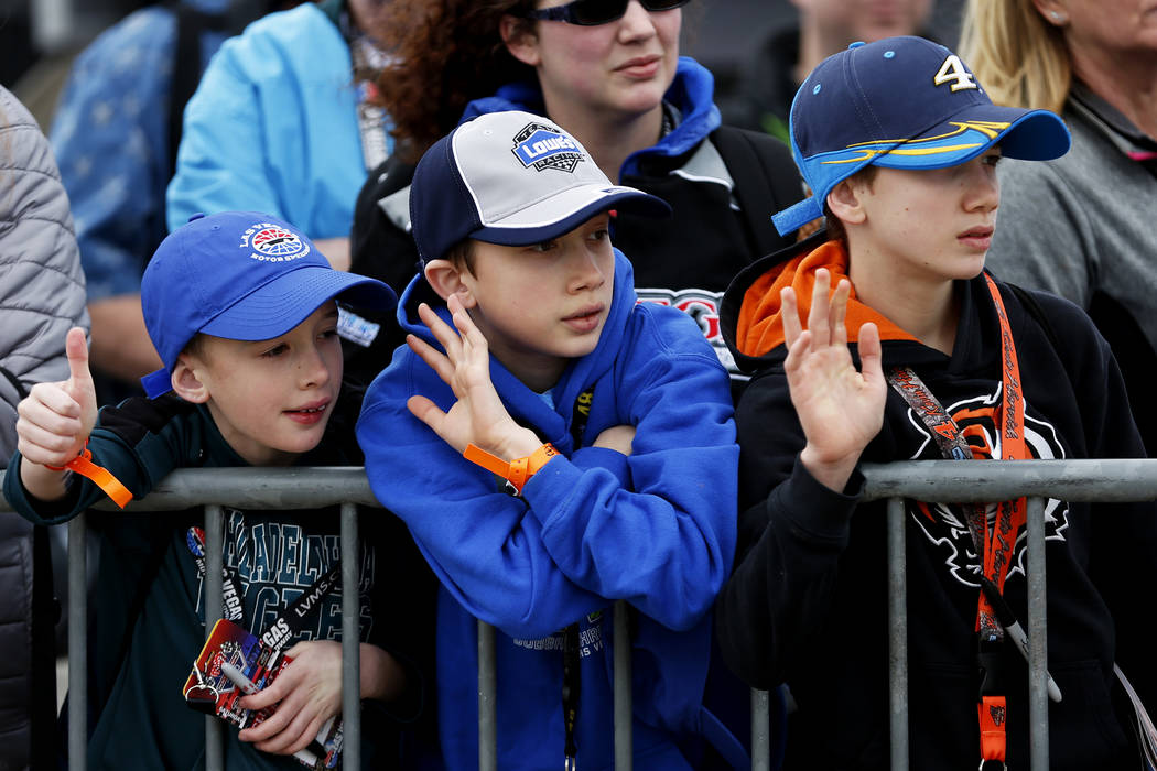 Patrick Walsh, 10, his brothers, Matthew, 11, and Zachary, 13, wave at drivers as they return to the Neon Garage at the Las Vegas Motor Speedway in Las Vegas on Saturday, March 3, 2018. Andrea Cor ...