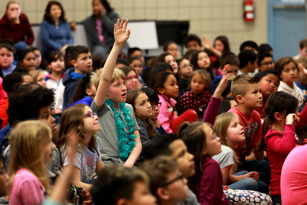 Spencer Hopkins, 11, raises his hand to ask Chad Trisef, author of the Oracle Series, a question about his books during Nevada Reading Week at Harriet Treem Elementary School in Henderson on Monda ...