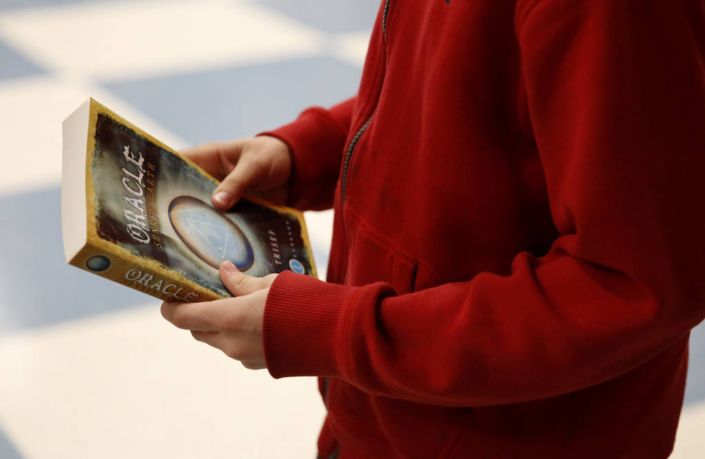 Kole Tippetts purchases a book by Chad Trisef, author of the Oracle Series, after his presentation for Nevada Reading Week at Harriet Treem Elementary School in Henderson on Monday, Feb. 26, 2018. ...
