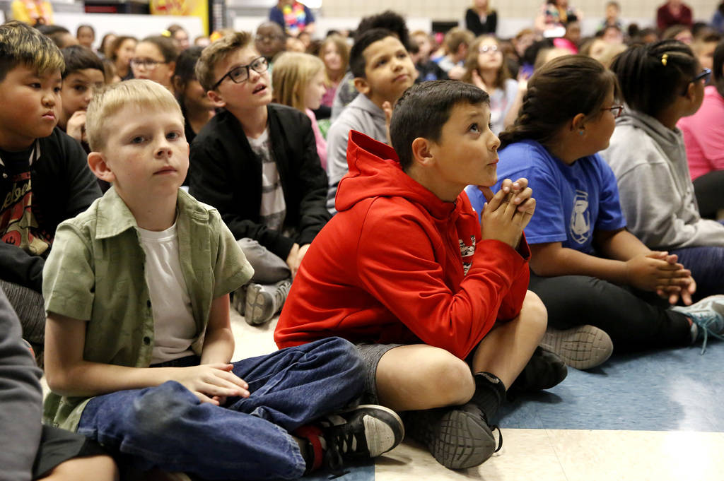 Norman Klens, 9, left, and Jacob VanNess, 9, center, attend a school assembly for Chad Trisef, author of the Oracle Series, during Nevada Reading Week at Harriet Treem Elementary School in Henders ...