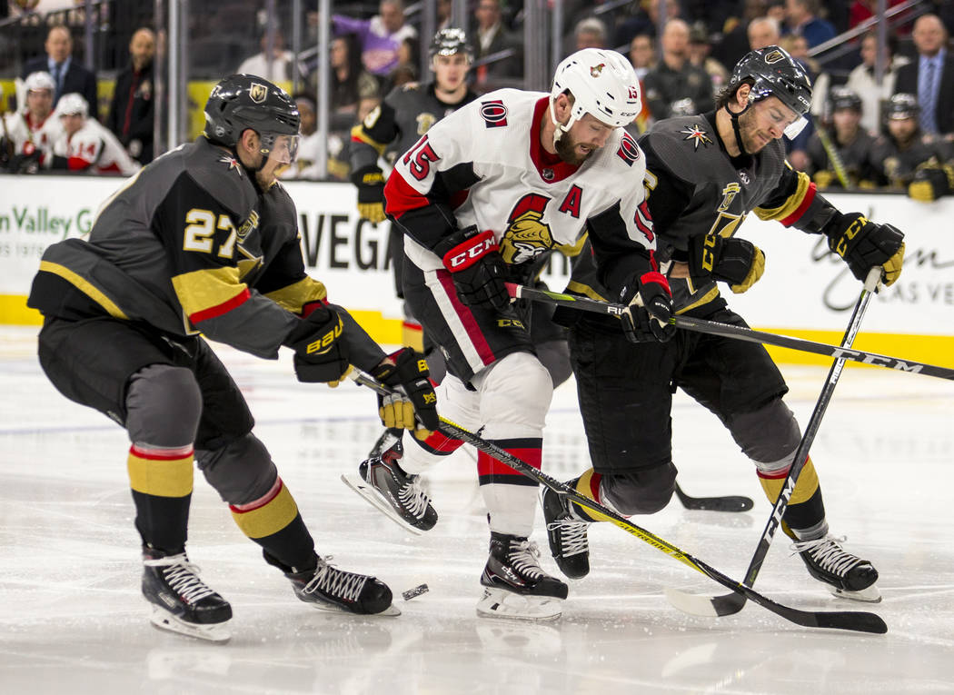 Ottawa Senators left wing Zack Smith (15) is sandwiched between Vegas Golden Knights defensemen Shea Theodore (27) and Colin Miller (6) during the third period of an NHL hockey game Friday, March  ...
