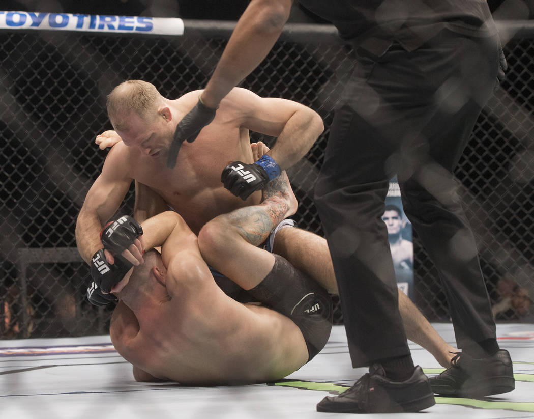 Zak Ottow, top, goes on the offensive against Mike Pyle during their welterweight matchup at UFC 222 at T-Mobile Arena on Saturday, March 3, 2018, in Las Vegas. Ottow beat Pyle via first round sto ...
