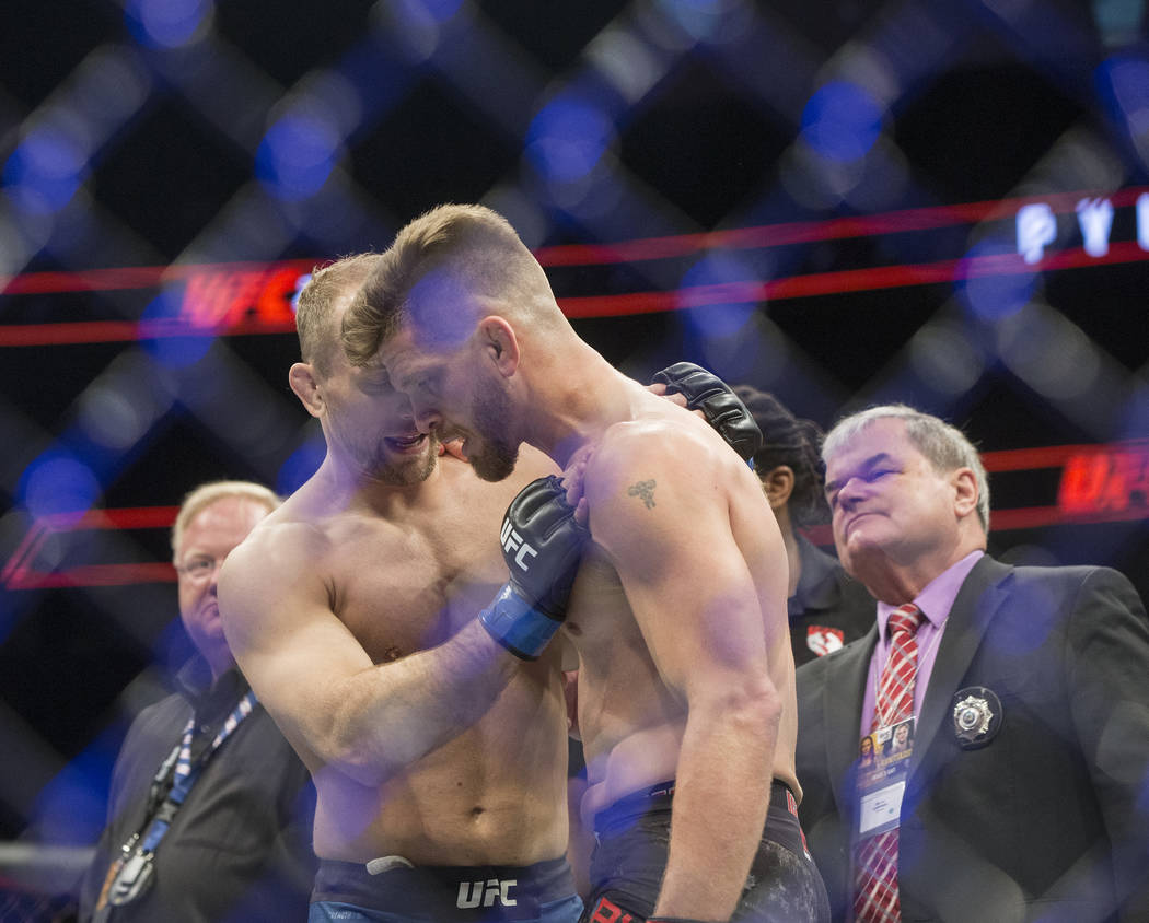 Mike Pyle, right, is consoled by Zak Ottow at the conclusion of their welterweight matchup at UFC 222 at T-Mobile Arena on Saturday, March 3, 2018, in Las Vegas. Ottow beat Pyle via first round st ...