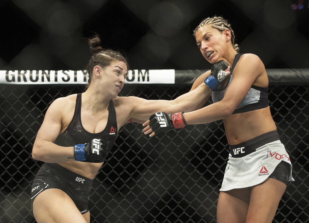 Mackenzie Dern, left, connects with a left hook against Ashley Yoder during their strawweight matchup at UFC 222 at T-Mobile Arena on Saturday, March 3, 2018, in Las Vegas. Dern defeated Yoder by  ...