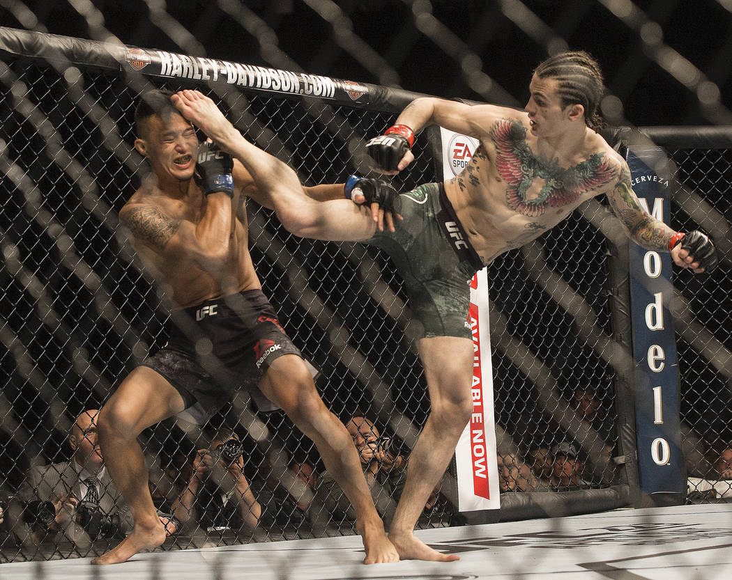 Sean O'Malley, right, connects with a kick to the head of Andre Soukhamthath during their bantamweight matchup at UFC 222 at T-Mobile Arena on Saturday, March 3, 2018, in Las Vegas. O'Malle ...