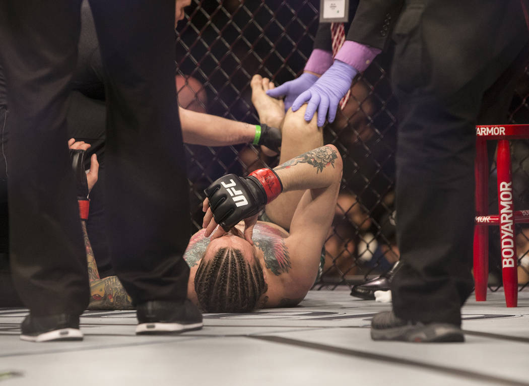 Sean O'Malley gets medical attention after his fight with Andre Soukhamthath on Saturday, March 3, 2018, in Las Vegas. O'Malley won by unanimous decision after suffering a serious foot inju ...
