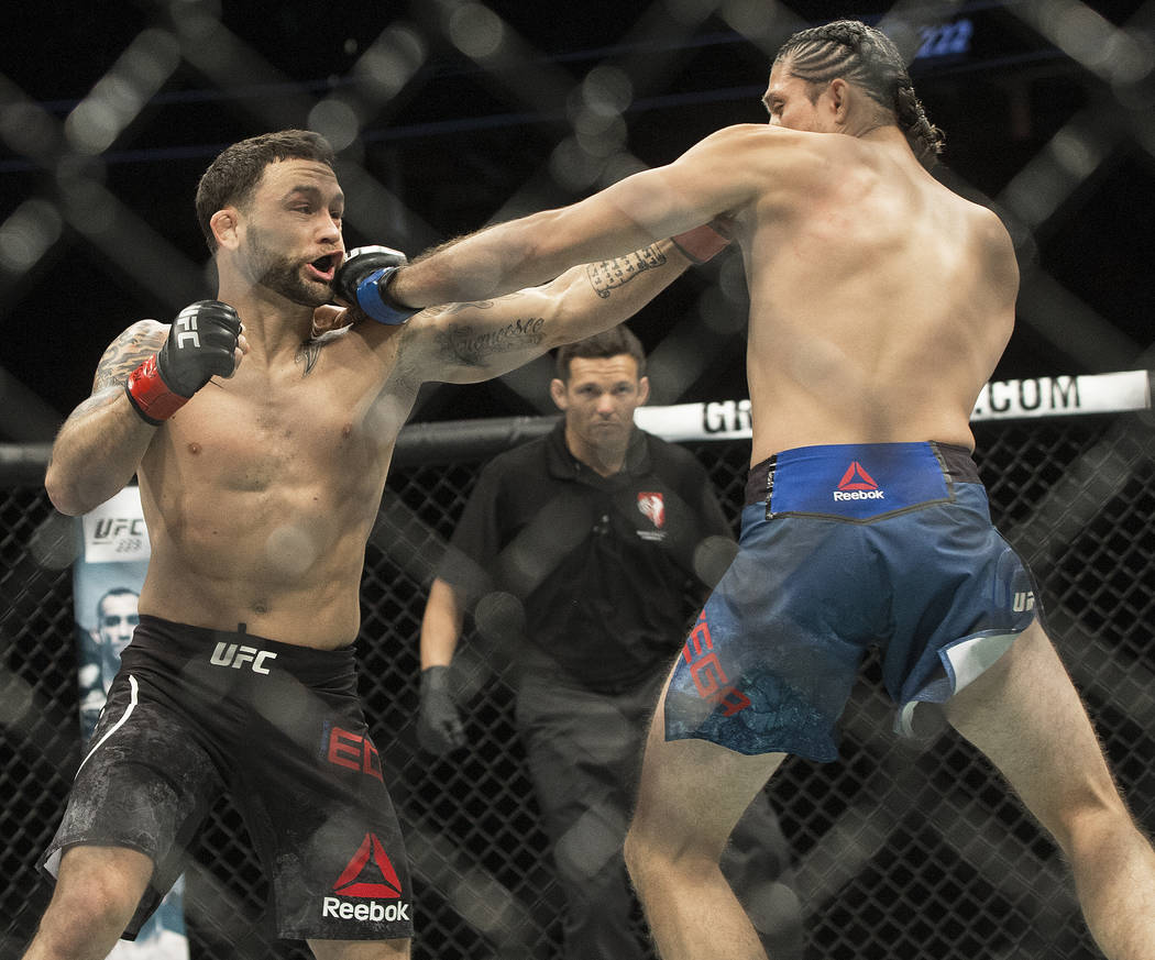 Brian Ortega, right,  connects with a jab against Frankie Edgar during their featherweight matchup at UFC 222 at T-Mobile Arena on Saturday, March 3, 2018, in Las Vegas. Ortega won by a first roun ...