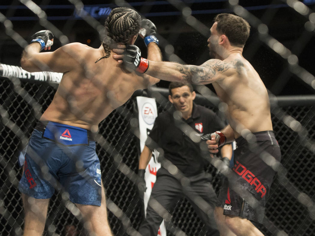 Brian Ortega, left, knocks Frankie Edgar to the ground with an uppercut during their featherweight matchup at UFC 222 at T-Mobile Arena on Saturday, March 3, 2018, in Las Vegas. Ortega won by a fi ...