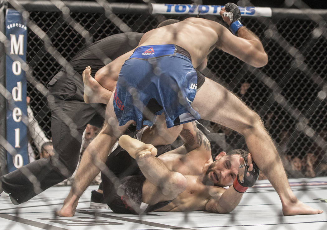 Brian Ortega, top, finishes off Frankie Edgar with a series of punches during their featherweight matchup at UFC 222 at T-Mobile Arena on Saturday, March 3, 2018, in Las Vegas. Ortega won by a fir ...