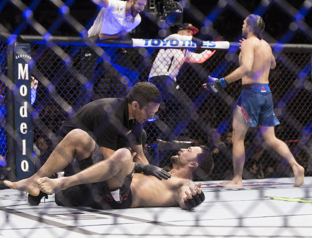 Frankie Edgar, left, is left dazed on the ground after being knocked out by Brian Ortega, right, in the first round of their featherweight matchup at UFC 222 at T-Mobile Arena on Saturday, March 3 ...