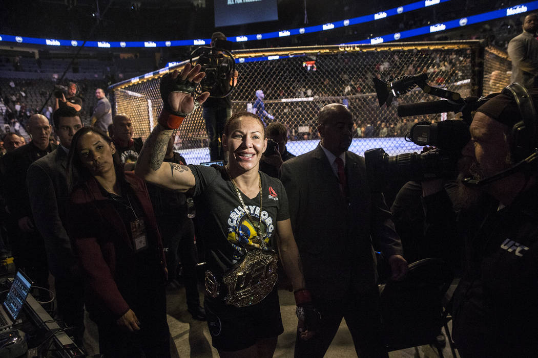 Cris Cyborg, middle, waives to fans after defending her featherweight title against Yana Kunitskaya via first round stoppage at UFC 222 at T-Mobile Arena on Saturday, March 3, 2018, in Las Vegas.  ...