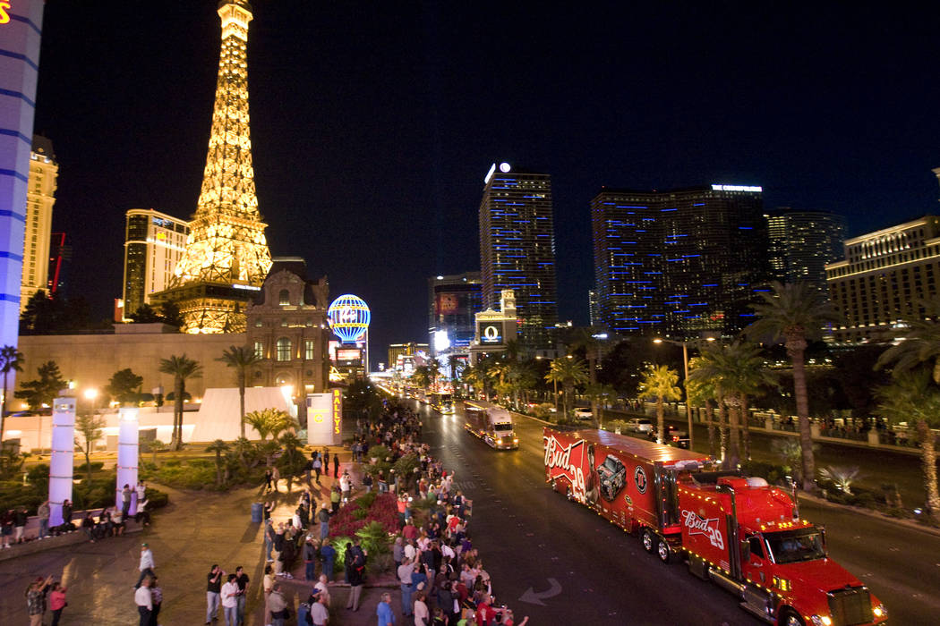 A crowd lines the Las Vegas Strip near Flamingo Road for during the semi-formal NASCAR parade of haulers, with the No. 29 Bud racecar hauler of driver Kevin Harvick shown in the foreground, on Thu ...