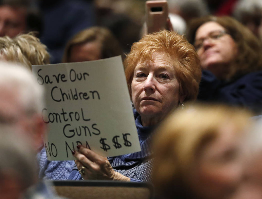 A protester waves a sign as U.S. Rep. Mike Coffman, R-Colorado, talks during a town hall meeting with constituents in a high school assembly hall Tuesday, Feb. 20, 2018, in Greenwood Village, Colo ...