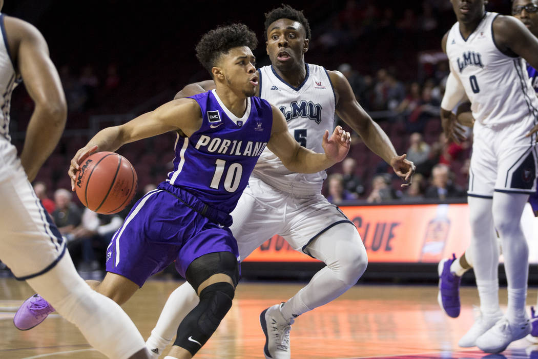 Portland Pilots guard Marcus Shaver Jr. (10) drives the ball to the basket against Loyola Marymount Lions guard James Batemon (5)in the first half ofthe West Coast Conference Men's Bas ...