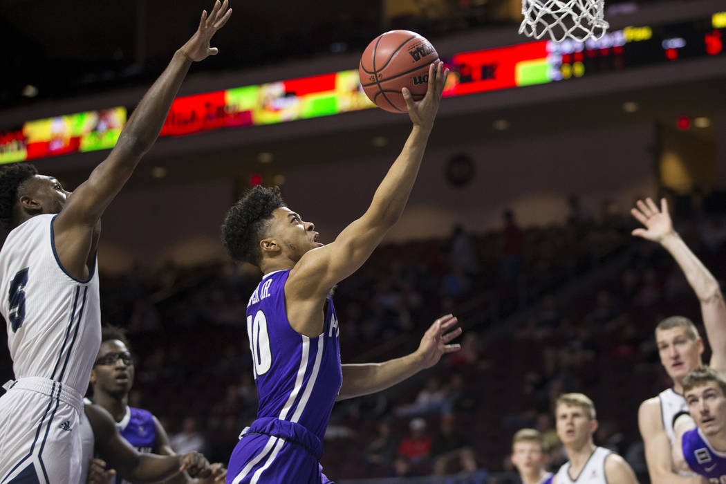 Portland Pilots guard Marcus Shaver Jr. (10) lays up the ball against Loyola Marymount Lions guard James Batemon (5) in the first half ofthe West Coast Conference Men's Basketball Tournament ...