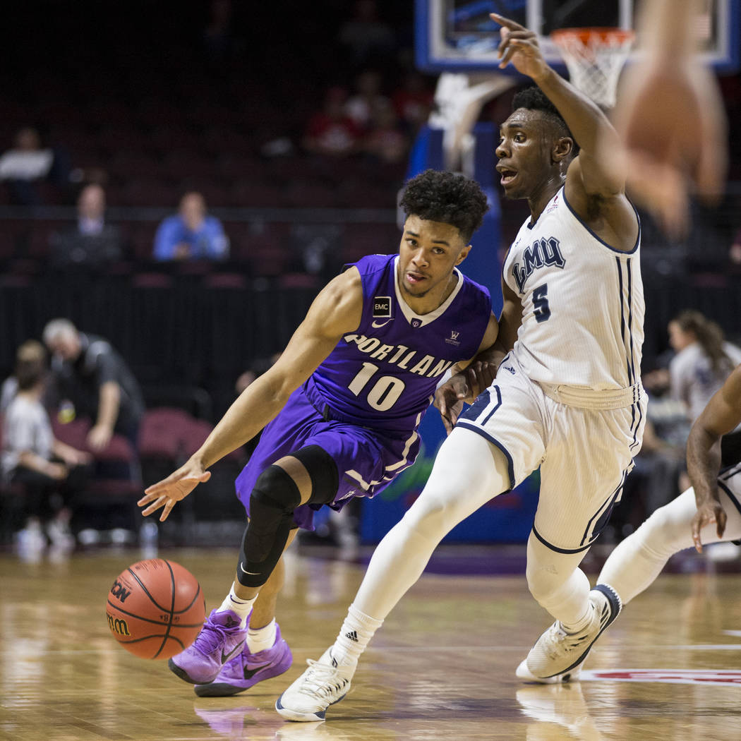 Portland Pilots guard Marcus Shaver Jr. (10) drives the ball under pressure from Loyola Marymount Lions guard James Batemon (5)in the first half ofthe West Coast Conference Men's Baske ...
