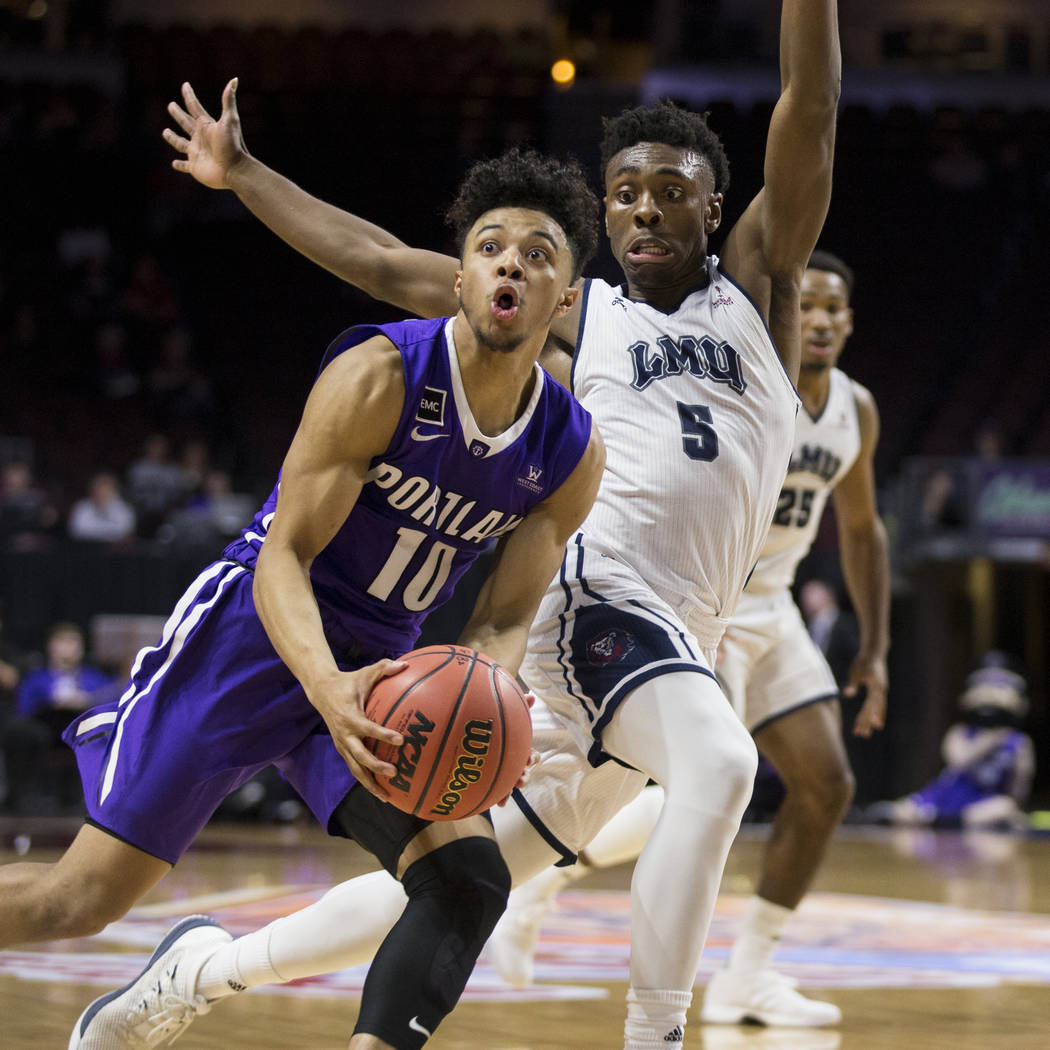 Portland Pilots guard Marcus Shaver Jr. (10) drives the ball under pressure from Loyola Marymount Lions guard James Batemon (5)in the first half ofthe West Coast Conference Men's Basketball To ...