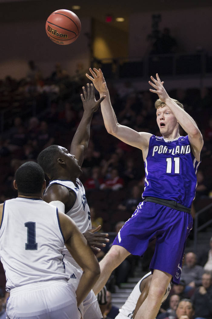 Portland Pilots guard Josh McSwiggan (11) makes a pass against Loyola Marymount Lions in the first half ofthe West Coast Conference Men's Basketball Tournament game at the Orleans Arena in L ...
