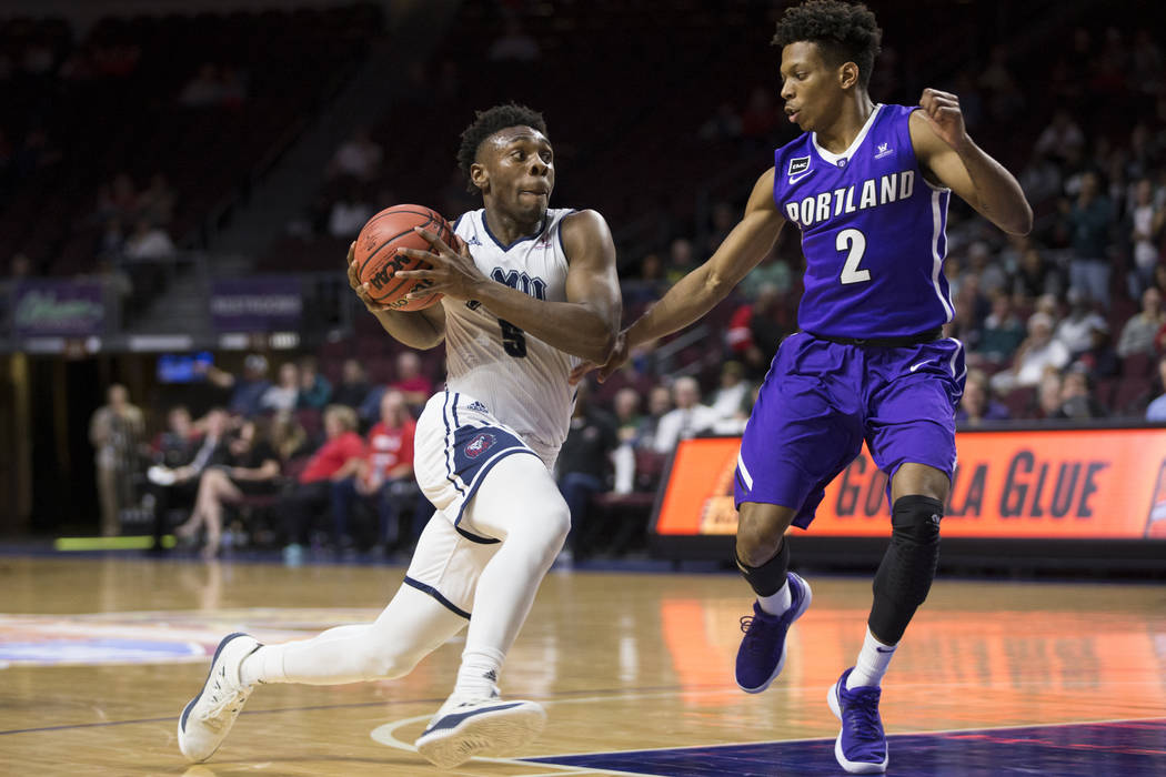 Loyola Marymount Lions guard James Batemon (5) drives the ball to the basket against Portland Pilots guard JoJo Walker (2) in the second half of the West Coast Conference Men's Basketball Tourname ...