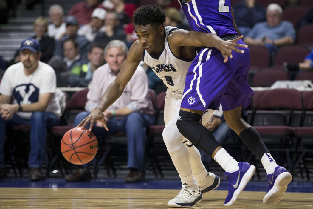 Loyola Marymount Lions guard James Batemon (5) drives the ball around Portland Pilots guard JoJo Walker (2) in the second half of the West Coast Conference Men's Basketball Tournament game at the  ...