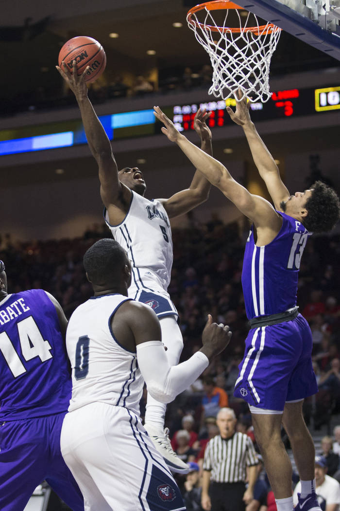 Loyola Marymount Lions guard James Batemon (5) takes a shot against Portland Pilots guard Franklin Porter (13) in the second half of the West Coast Conference Men's Basketball Tournament game at t ...