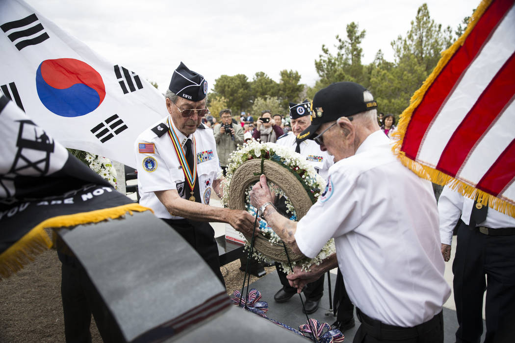 Korean War veterans Lee Mowery, left, and Stan Croonquist, present a memorial wreath at the unveiling of the Korean War memorial monument at the Southern Nevada Veterans Memorial Cemetery in Bould ...
