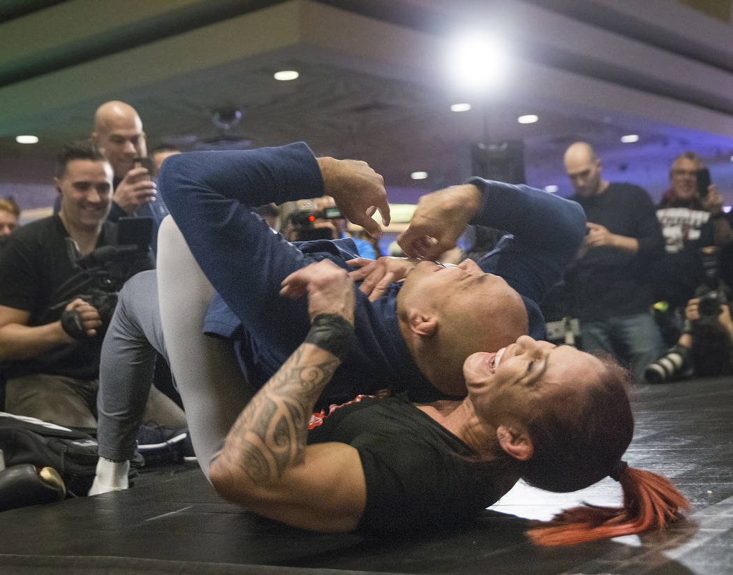 Cris Cyborg, right/bottom, UFC women's featherweight champion, warms up with coach and UFC icon B.J. Penn during open workouts leading up to Saturday's UFC 222 on Thursday, March 1, 2018, at the M ...