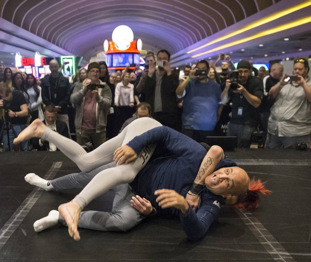 Cris Cyborg, top, UFC women's featherweight champion, takes down coach and UFC icon B.J. Penn during open workouts leading up to Saturday's UFC 222 on Thursday, March 1, 2018, at the MGM Grand hot ...