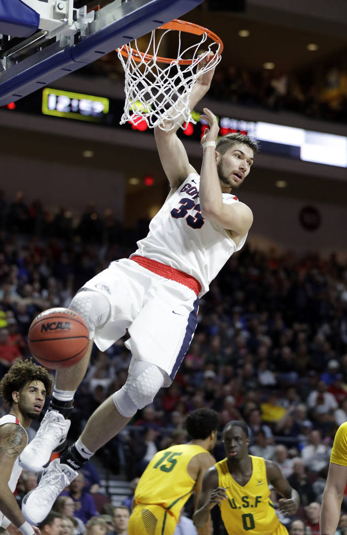 Gonzaga's Killian Tillie hangs on the rim after dunking during the second half of a West Coast Conference tournament NCAA college basketball game against San Francisco Monday, March 5, 2018, in La ...