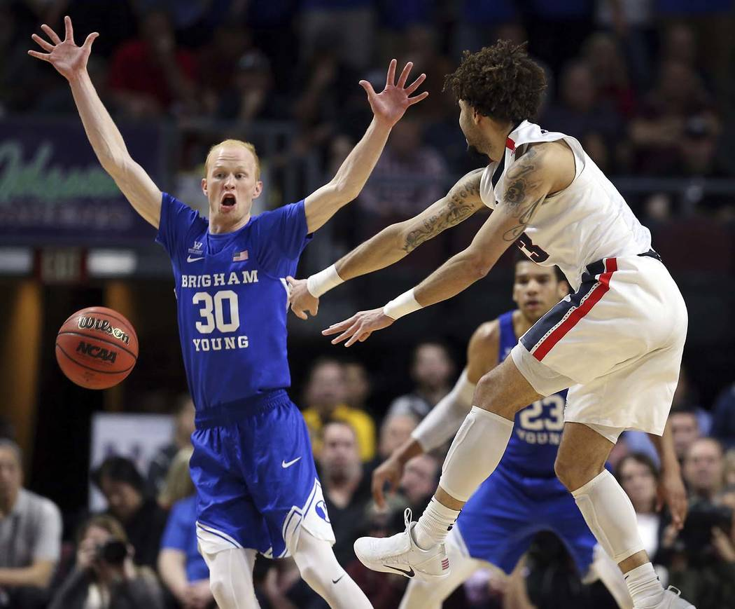 Gonzaga's Josh Perkins passes under BYU's TJ Haws (30) during the first half of the West Coast Conference tournament championship NCAA college basketball game Tuesday, March 6, 2018, in Las Vegas. ...