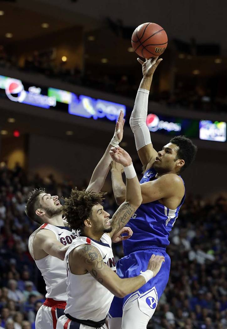 BYU's Yoeli Childs shoots over Gonzaga's Killian Tillie, left, and Josh Perkins during the first half of the West Coast Conference tournament championship NCAA college basketball game Tuesday, Mar ...