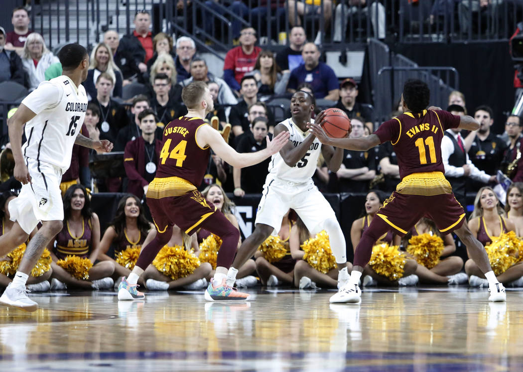 Arizona State's  Kodi Justice (44) and Shannon Evans II (11) defend Colorado Buffaloes' McKinley Wright IV (25) as he tries to pass the ball to his teammate Dominique Collier (15) during an NCAA c ...