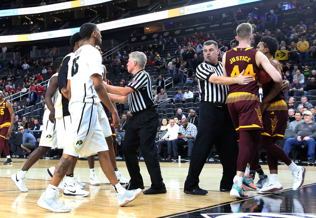Referees tries to break up a fight between Colorado Buffaloes' players, left, and Arizona State players during an NCAA college basketball game in the first round of the Pac-12 tournament on Wednes ...