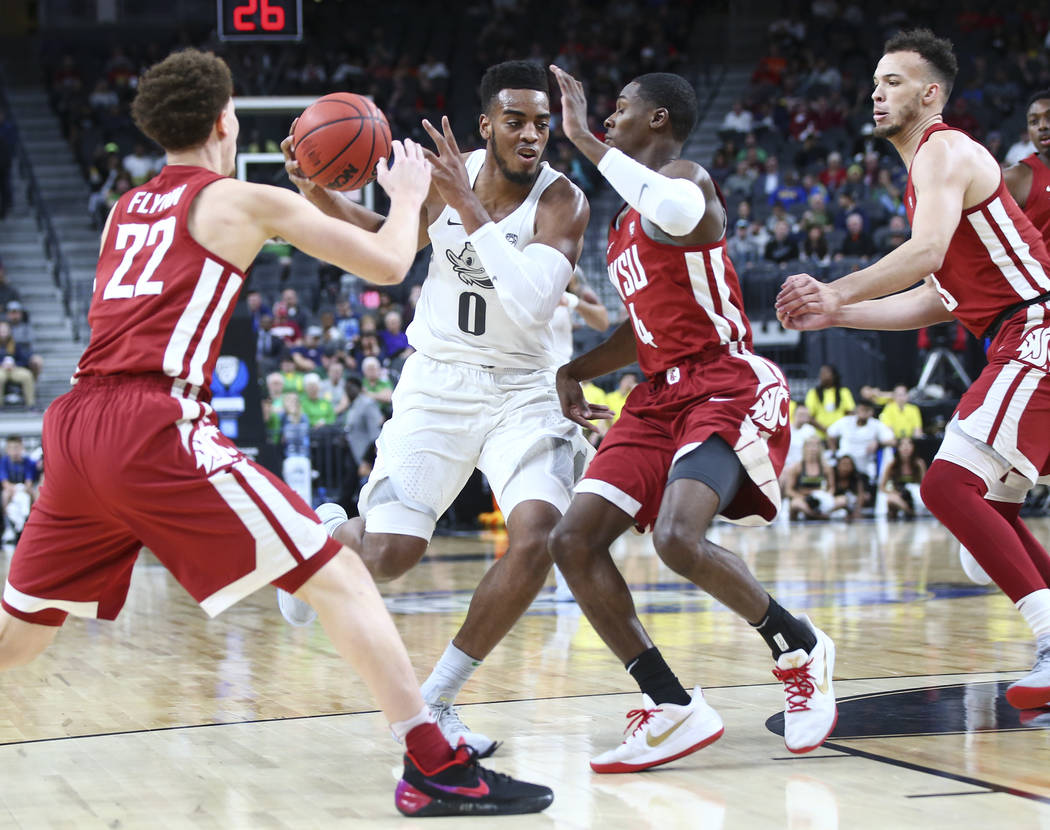 Oregon Ducks forward Troy Brown (0) drives between Washington State Cougars guards Malachi Flynn (22) and Viont'e Daniels (4) during the Pac-12 basketball tournament at T-Mobile Arena in Las Vegas ...