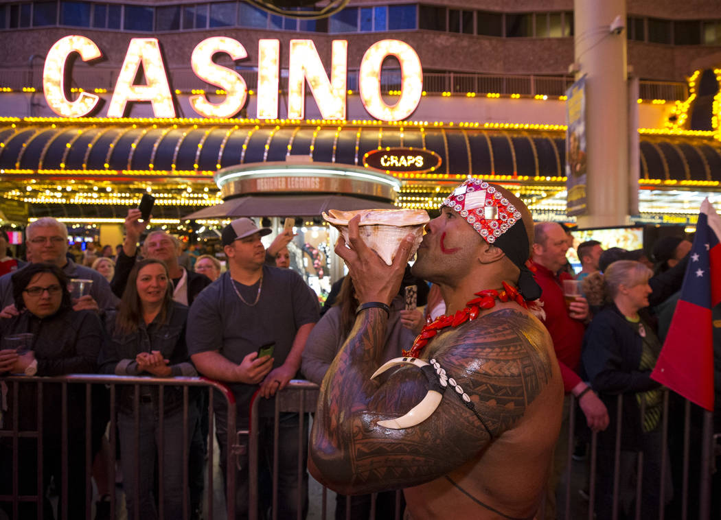 Hio Pelesasa blows into a conch shell as he marches with the Samoan Rugby team during the Parade of Nations at the Fremont Street Experience in downtown in Las Vegas on Thursday, March 1, 2018. Ri ...